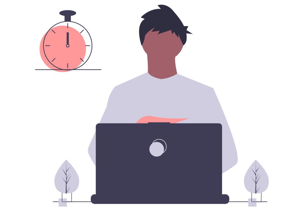 時計の前に座った男性がパソコンを操作している